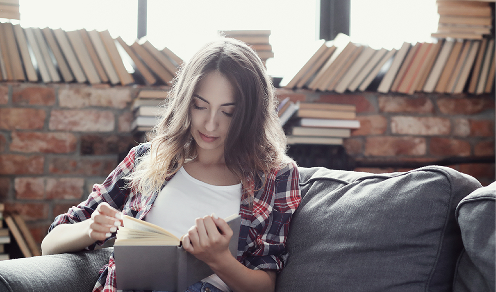 young-teenager-girl-reading-book-home
